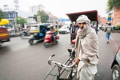 Åldringen cyklar rickshawen som söker efter passageraren på trafikgatan Royaltyfri Fotografi