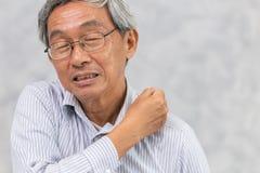 Åldringen drar tillbaka halsen, och skuldran smärtar genom att använda handen för att massera arkivfoton