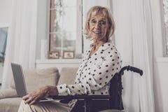 Åldringen frilansar sammanträde för arbetarhandstilartikel i rullstol royaltyfria bilder