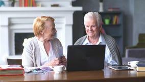 Åldringen kopplar ihop att ha gyckel, i att meddela med familjen på internet i bekväm vardagsrum stock video