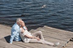 Åldringen kopplar ihop att koppla av, medan sitta på trottoar på flodstranden Fotografering för Bildbyråer