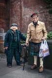 Åldringen kopplar ihop i skotsk klänning på gatan Royaltyfria Bilder