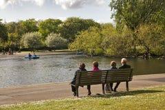 Åldringen kopplar ihop sammanträde på en bänk på en sjö Fotografering för Bildbyråer