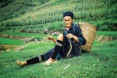 åldringen svärtar kvinnan för hmongstammedlemmen som hem vilar, efter ett långt dagsverke på hans lantgårdsnurr har dragagit fotografering för bildbyråer