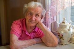 Åldringen tröttade kvinnasammanträde på en tabell med en kokkärl av te arkivfoto