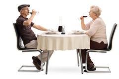 Åldringpar som dricker rött vin på ett datum royaltyfria foton