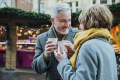Åldringpar som dricker varma drinkar på julmarknaden! arkivbilder