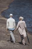 Åldringpar som går på flodkust på dagen Royaltyfria Foton