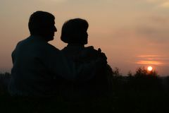Åldringpar som ser solnedgång royaltyfria bilder