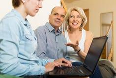 Åldringpar som talar med anställd med bärbara datorn Fotografering för Bildbyråer