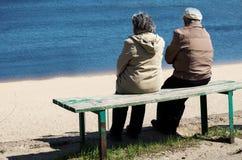 Åldringparet vilar på bänk nära floden Fotografering för Bildbyråer