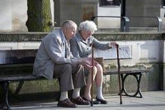 Åldringparsammanträde på bänk parkerar in Royaltyfri Foto