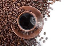 Ånga över koppen av varmt kaffe, spridda kaffebönor som isoleras på vit Arkivfoton