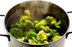 Veganmat: ånga broccoli i en inoxkruka Arkivbilder