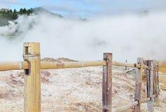 Ånga den vulkaniska kratoren som är bifogad vid ett trästaket royaltyfri fotografi