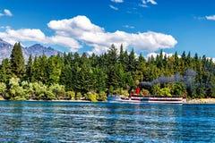 Ånga-drivit skepp på sjön Wakatipu som omges av barrskogen i Queenstown Royaltyfri Foto