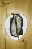 Ånga med makrillen i den vita maträtten på den wood tabellen Royaltyfri Fotografi
