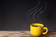 Ånga modellen på en svart tavla bak en trätabell med koppen av Fotografering för Bildbyråer
