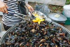 Ångade Black Sea musslor i sås med grönsaker Royaltyfri Bild