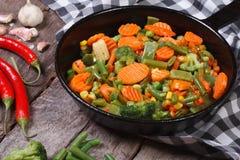Ångade grönsaker i en panna på tabellen. Arkivbilder