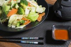 Ångade grönsaker på en svart platta Arkivfoton