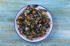 Ångade musslor i vitt vin med örter, skaldjur Tjänat som i den vita plattan, upp sikt på blå träbakgrund Fotografering för Bildbyråer