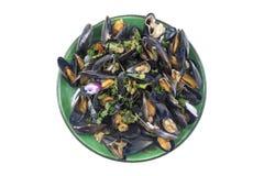 Ångade musslor i vitt vin med örter, skaldjur Tjänat som i grön platta, upp sikt på vit bakgrund Royaltyfri Foto