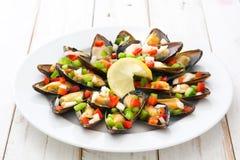 Ångade musslor med peppar och löken på vitt trä Royaltyfria Foton