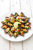 Ångade musslor med peppar och löken på vitt trä Arkivbild