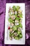 Ångade musslor med sallad på en platta Arkivbild
