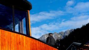 Ångarekapten On The Deck med dolda fjällängar för snö bortom royaltyfria bilder