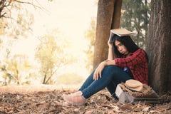Ångestkvinnan om henne som studerar att sitta som är ensamt under det stora trädet parkerar på fotografering för bildbyråer