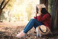 Ångestkvinnan om henne som studerar att sitta som är ensamt under det stora trädet parkerar på arkivbild