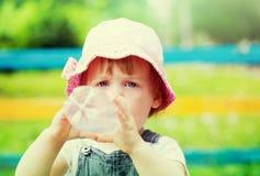 2 år behandla som ett barn drinkar från flaskan Arkivbilder