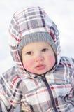 1 år behandla som ett barn med rosiga kinder i vinter utomhus Arkivfoton