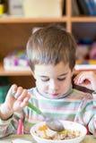 År för en pojke som på åldern av äter välling i dagiset Arkivfoton