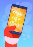 År för kort för hälsning för glad jul för Santa Claus Hand Hold Cell Smart telefon lyckligt nytt Royaltyfri Bild