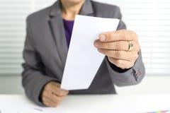 55 år gammal kvinnlig affärskvinna rymmer en räkning Arkivfoto