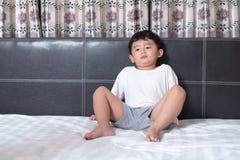 3 år gammal liten sjuk eller för sjukdom asiatisk pojke hemma på sängen, den ledsna ungen som lägger att vila på vit säng med kud royaltyfria bilder