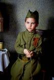 År gammal pojke i den ryska militära formen som är härlig med blåa ögon Royaltyfri Foto