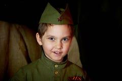 År gammal pojke i den ryska militära formen som är härlig med blåa ögon Royaltyfri Bild