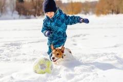 4 år gammal pojke som spelar fotbollfotboll med hans hund på snö royaltyfri bild
