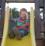 5 år gammal redheaded lycklig pojke sitter på en glidbana och le arkivfoton