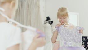 6 år gammal ung dam som framme försöker på den eleganta klänningen av en spegel stock video