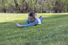 7 år gammalt barn som ligger på gräset i, parkerar arkivbilder