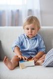 2 år gammalt lyckligt behandla som ett barn pojkesammanträde på soffan Arkivfoton