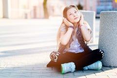 10 år gammalt lyckligt flickabarn lyssnar till musiken Arkivfoton