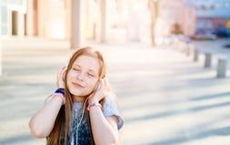 10 år gammalt lyckligt flickabarn lyssnar till musiken Royaltyfri Fotografi
