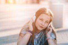 10 år gammalt lyckligt flickabarn lyssnar till musiken Arkivbild