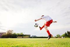8 år gammalt pojkebarn som sparkar bollen på spelplan Royaltyfri Bild